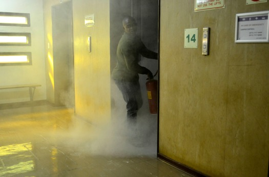 SMOKEY: Elevator technician trying to extinguish the flames in Lift B on 14 floor, University Corner. Photo: Pheladi Sethusa