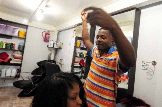 Evans Emeafa does a client's hair at his family owned beauty salon in Braamfontein, 7 April 2014. The area has been nicknamed little Lagos due to the amount of Nigerian owed businesses in the area. Picture: Tracy Lee Stark