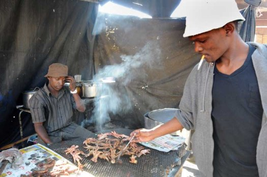 Musa Bhengu looks on as the customer picks the braaied chicken feet at Bara taxi rank, 28 May 2014. Bhengu has been supplying hungry commuters since 1999. Picture: Nigel Sibanda