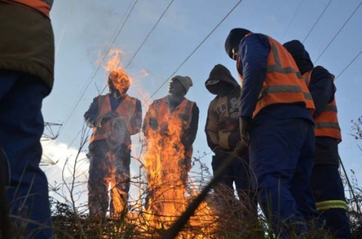 Construction workers stand around a fire to keep warm, 06 June 2014, in Industria West, Johannesburg. Residents of Johannesburg are expecting temperatures to drop as a cold front passes through the country. Picture: Alaister Russell