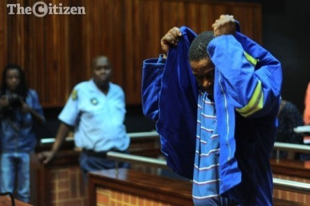 Truck driver Isaac Maruding attempts to cover his head during a court adjournment of his bail application at the Palm Ridge Magistrate's court, 22 October 2014. Maruding is appearing on charges of culpable homicide. Picture: Refilwe Modise